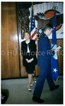 Cadet Walks Past Unidentified Woman While Carrying A Certificate
