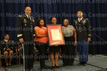 [Cadet poses with family and ROTC leadership at the 2016 Army ROTC Commissioning Ceremony]