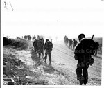 Japanese American 100th Infantry Battalion marching up dusty road
