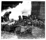 Soldiers of the 161st Chemical Smoke Generating Company, U.S. Third Army, move a barrel of oil in preparation to refilling an M-2 smoke generator, which spews forth a heavy cloud of white smoke. Waller Fengen, Germany, 12/11/1944