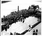 "Heavily laden American negro troops walk across the desk of a British ""Zed Lighters"""