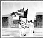 "A four man color guard stands alert as the bugle sounds ""Attention!"" to start a regimental review at Camp Robert Smalls, home of the All-Negro regiment here at the U.S. Naval Training Station"