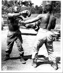 Pfc. Fred Hayes, Quincy, Florida, and Pvt. Joe Turner, Baton Rouge, Louisiana, playing throwing the leather at one another…New Guinea