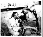 Sgt. Robert D. Gibson; Corp. Melbria Gray; and Corp. Willie Lagree repair axel of 3 1/2 ton truck, New Guinea