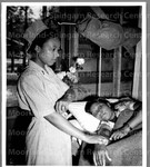 2nd Lt. Marjorie Meyers of N.Y. City attends sister nurse 2nd Lt. Claudia E. Matthews of Dallas, Texas in the hospital.