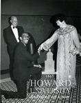 J. Clay Smith, Jr. kneeling with Geraldine Wood Pittman (Chairman of the Board of Howard University