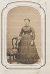 Unidentified woman posing next to chair