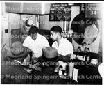 2 Men helping customers standard drug store (NNA)